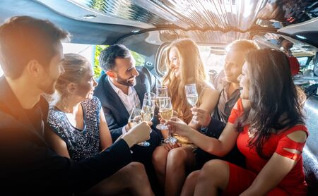 Group of women and men clinking glasses in a limousine having fun and being happy Reklamní fotografie