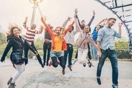Amigos de la diversidad saltando en el parque siendo alegre y despreocupado