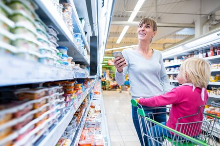 Woman with her child in fresh department of supermarket having the shopping list on her phone Stock Photo