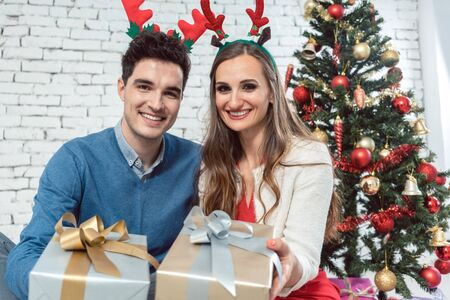 Couple with Christmas presents in silver and gold and horns looking into camera