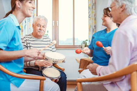 Seniors in nursing home making music with rhythm instruments as musical therapy