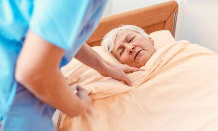 Caregiver pulling blanket over sleeping senior in pensioners home for better sleep Standard-Bild - 132332103