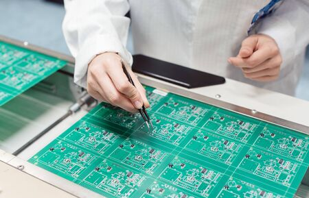 Technician assembling electronic product by inserting components into board on manufacturing line