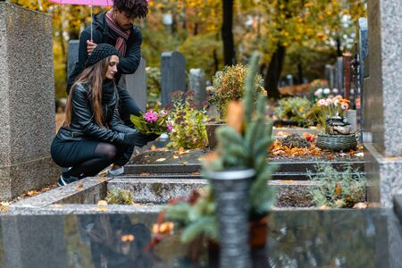 Couple in grief on a cemetery in fall while it is raining Stock fotó