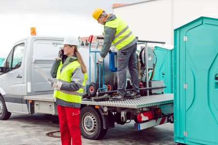 Workers taking care of a delivery of mobile rental toilets by truck