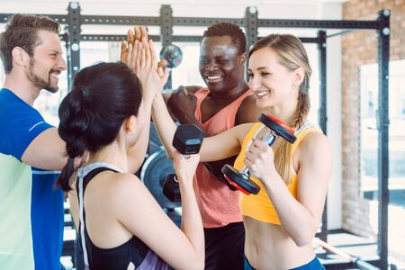 Four friends in the gym having fun stacking hands Фото со стока