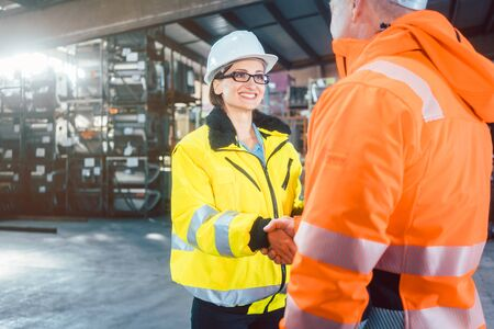 worker and customer in logistics warehouse having handshake to seal a deal Foto de archivo