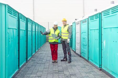 Trabajadores que revisan los baños portátiles con fines de alquiler. Foto de archivo
