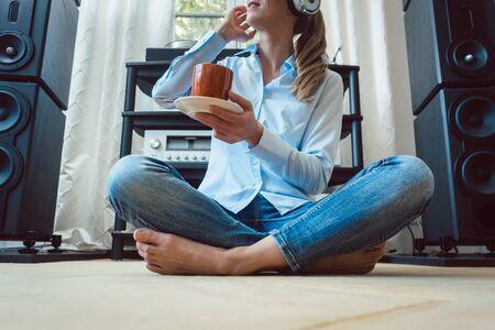 Frau, die zu Hause Musik von einer Hi-Fi-Stereoanlage hört