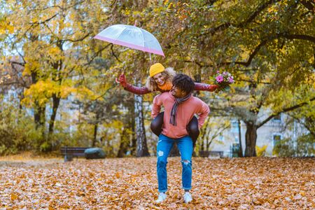 Black man carrying his Caucasian girl piggyback in fall both being joyful