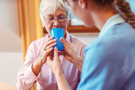 Caregiver helping senior woman drinking giving her a cup of water and holding it