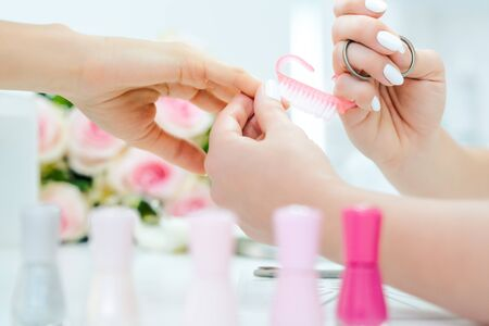 Nails of woman being prepared for manicure with brush