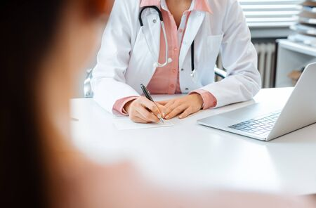 Close-up of doctor taking notes while having appointment with woman patient