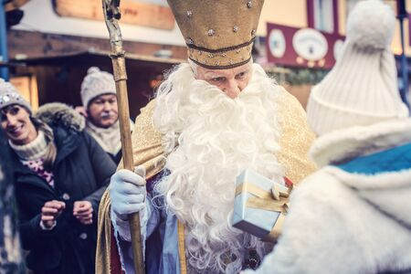 St Nicholas and an extended family with child on the Christmas market 版權商用圖片