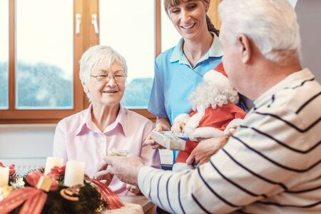 Seniors in nursing home exchanging presents for Christmas with candles on the table