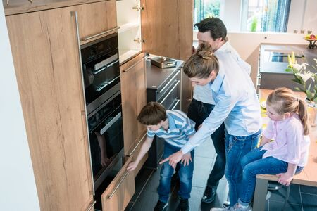 Scene in a kitchen showroom, family shopping for a new model looking at the equipment 版權商用圖片