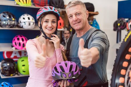 Customer choosing bicycle helmet in a shop with help from the owner