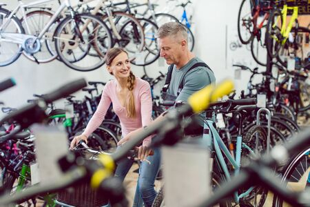 Salesman helping woman customer in bike shop to find the right bicycle 版權商用圖片