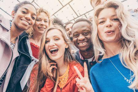 Wesołych przyjaciół z różnych grup etnicznych patrzących w kamerę