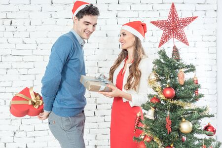 Woman receiving Christmas present from her man in front of Christmas tree Stock fotó