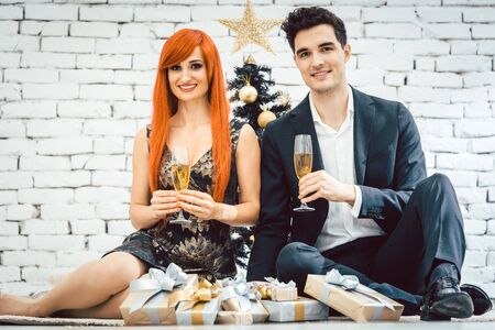 Ginger haired woman and man clinking glasses for Christmas in front of black tree