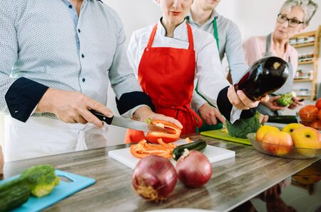 Man in training kitchen cutting vegetables under watchful eye of competent dietician