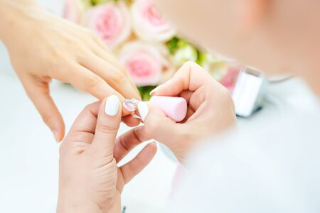 Experienced nail technician applying nail color to fingernails
