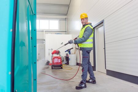 Worker cleaning a rental or mobile toilet with water hose Stock fotó