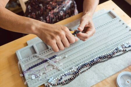 Close-up of woman making a necklace from gemstones putting them on string Imagens