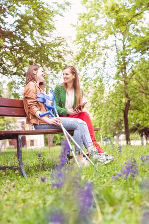 Two women, one healthy and one with a sprained foot, on a bench in the park