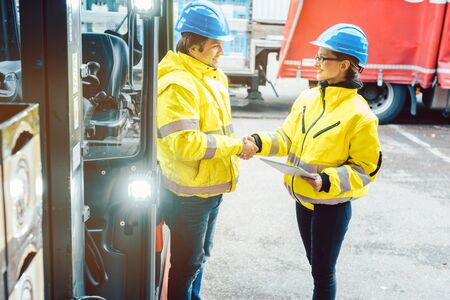 Worker and manager shaking hands at distribution center behind a forklift