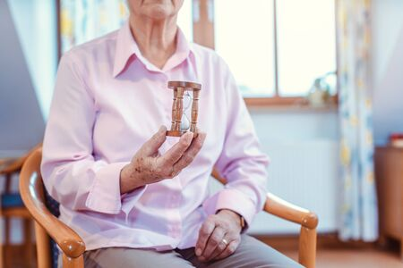 Senior in nursing home holding a hourglass - time is running up quickly Stock Photo