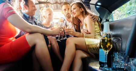 Group of party people in a limo drinking looking at the camera Standard-Bild