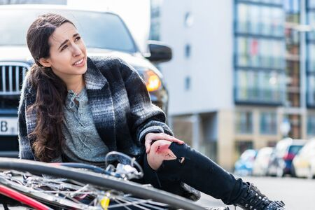 Young woman suffering severe pain caused by knee strain or fracture after falling down from her bicycle in accidental collision with a 4x4 car