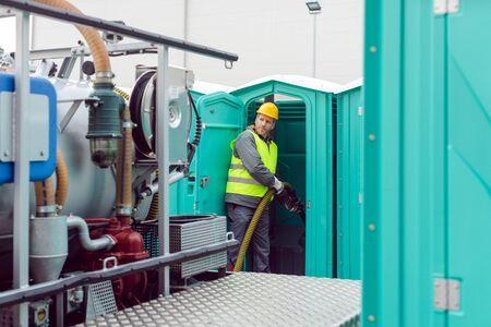 Trabajador bombeando las heces del inodoro de alquiler para su eliminación y limpieza