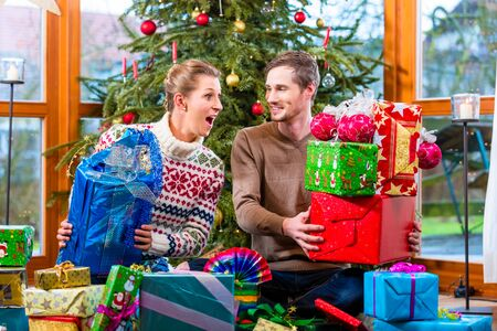 Happy man and woman sitting with presents under Christmas tree Stock Photo