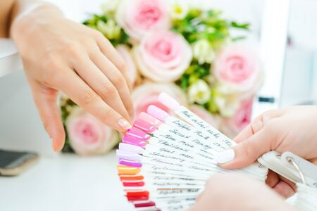 Woman during manicure choosing a nail color from many