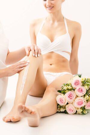 Hair removal using creme on legs of beautiful woman in beauty parlor Zdjęcie Seryjne