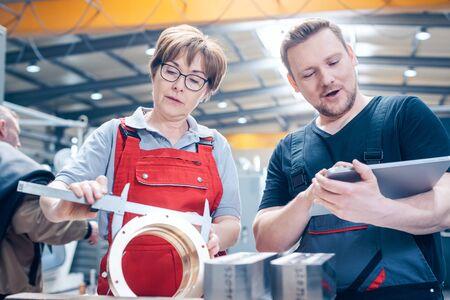 Workers measuring a metal workpiece with gauge Reklamní fotografie