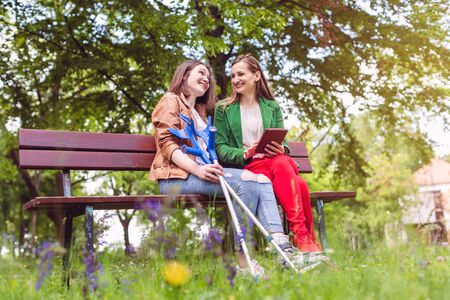 Two friends in a park, one with a broken feet and crutches reading a book