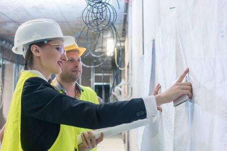 Builder and construction worker looking at building blueprint pinned to a wall Фото со стока
