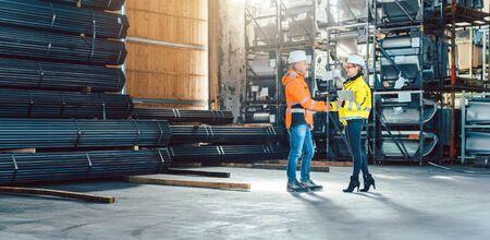 Handshake of worker and customer in logistics warehouse Foto de archivo