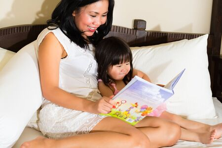Happy mother and daughter reading story book at home
