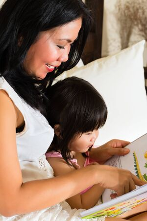 Smiling mother and daughter reading story book at home
