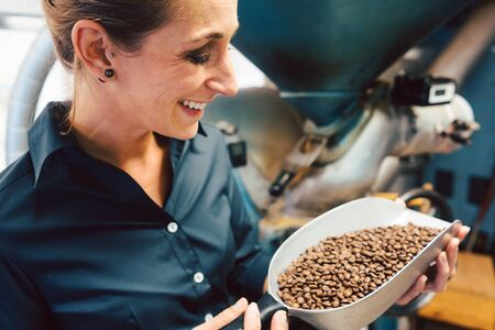 Woman in coffee roastery with fresh beans full of aroma