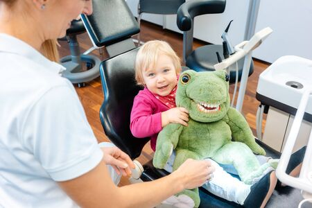 Little girl having fun with plush toy visiting the dentist