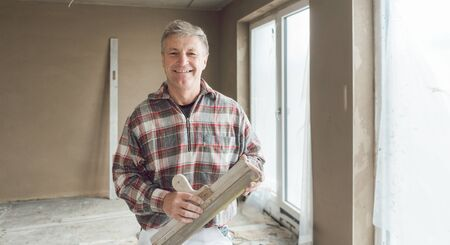 Friendly plasterer man in the interior of newly constructed house Banco de Imagens