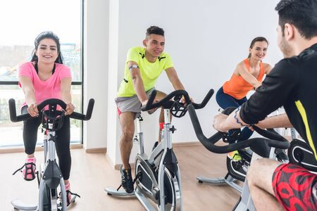 Young friends group exercising on bicycle at the fitness center Stock Photo