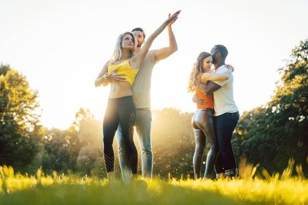 Group of people dancing Kizomba in golden sunset