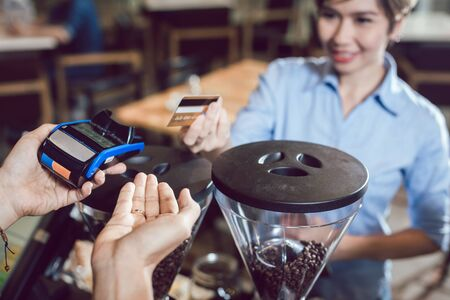 Barista holding a credit card reader machine and female customer making payment with card